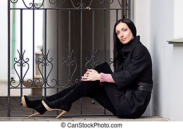 young woman sits near a wall