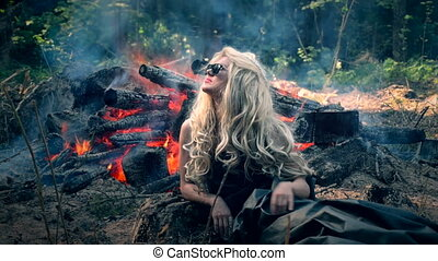 Young woman sits near the bright bonfire and looks around....
