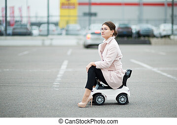 young woman sits on a children's plastic car and looks into the distance