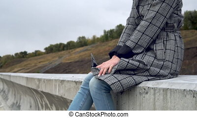 Young woman sits on a concrete fence in the wind and shakes her legs