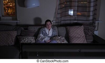 Young woman sits on a couch in front of the TV in the dark