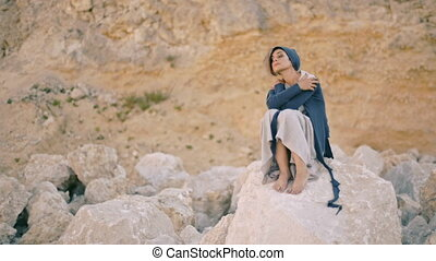 young woman sits on a rock in the background of the mountains