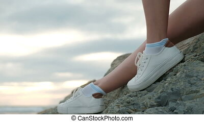 Young woman sits on beach on summer evening outdoors.