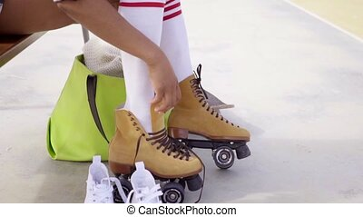 Young woman sits on bench to tie her skates