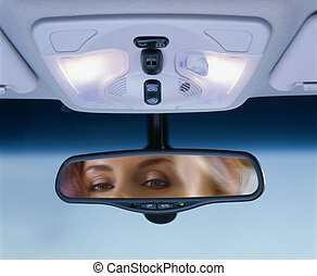 rear-view mirror - Young woman sits on driver\'s seat and...