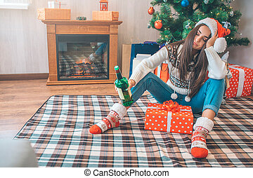 Young woman sits on floor and sleeps. She holds green bottle of alcohol in hand. There is a box with present between her legs. She is drunk.