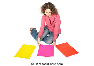 young woman sits on floor with three multi-coloured sheets of paper
