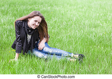 Young woman sits on lawn