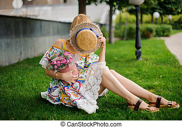 young woman sits on lawn with bouquet and covers her face with hat