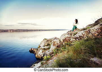 Young woman sits on rock and enjoys view of river at sunset