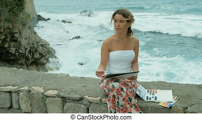 Young woman sits on seashore and paints with watercolors outside.