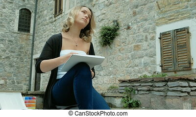 Young woman sits on stones of old city and paints with watercolors. Attractive blond female.