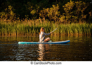 young woman sits on sup board with paddle in her hands and floats on the river