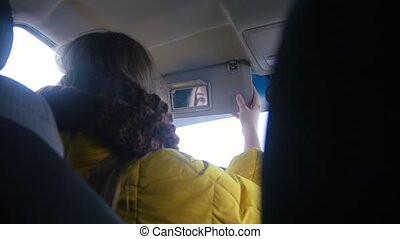 Young woman sits on the driver's seat, puts down the visor...