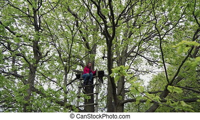 Young woman sits on top of a wooden staircase in the mighty oak foliage and smiles