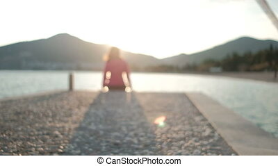 Young woman sits turning to face nature on stones on...