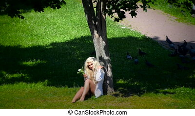 Young woman sits under the tree. Blonde female beckoning to...
