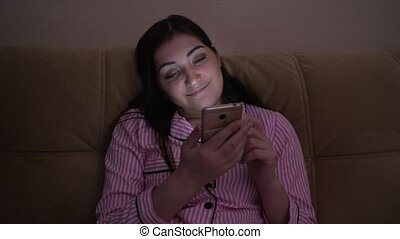 young woman sits with a phone on the couch and smiles