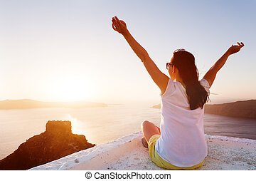 Young woman sits with hands up and admires the Caldera view on Santorini, Greece. Sunset
