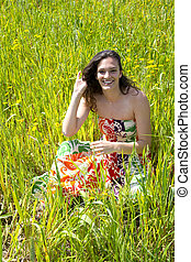 Young woman sitted in a field of flowers.