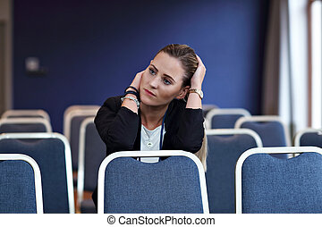 Young woman sitting alone in conference room