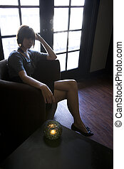 Young woman sitting alone in dark room thinking