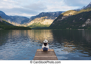 Young woman sitting alone on wooden pier, looking lake and mountain view in summer at Hallstatt, Austria