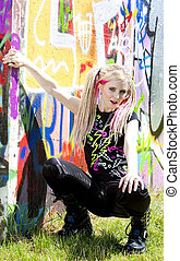 young woman sitting at graffitti wall