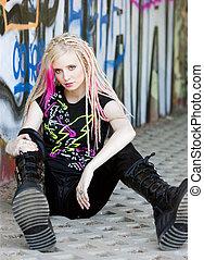 young woman sitting at graffitti wall