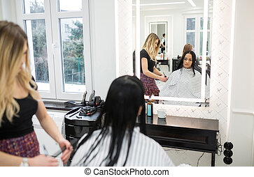 Young woman sitting at hairdresser salon having hair cut