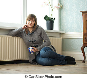 Young woman sitting at home with a cup of tea