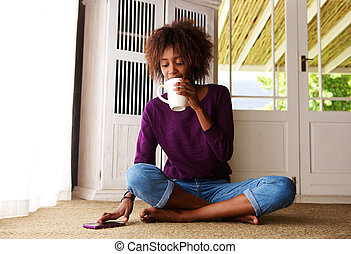 Young woman sitting at home with coffee and mobile phone