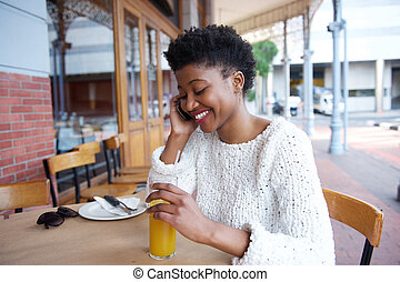 Young woman sitting at outdoor cafe talking on cell phone - ...