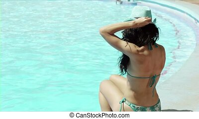 young woman sitting at resort pool