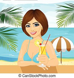 woman sitting at table at the beach drinking cocktail
