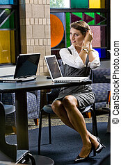 Young woman sitting at table with laptop computer