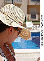 Young woman sitting at the pool side