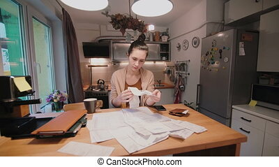 Young woman sitting at the table in kitchen and calculating bills after shopping. Home accounts department.