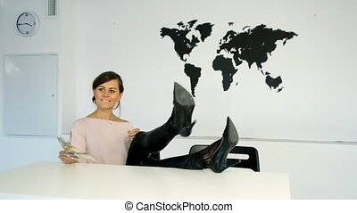 Young woman sitting at the table on the background of world map