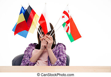Young woman sitting at the table with international flags
