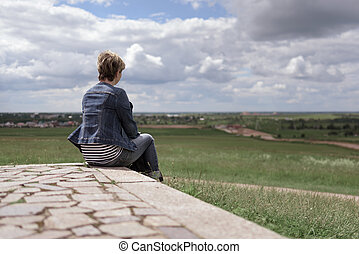 Young woman sitting back on stone tile and looking into the distance at the fields against the beautiful sky