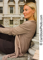 young woman sitting by a pillar.