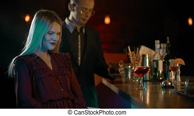 Young woman sitting by the bartender stand - a man comes to her and they start talking