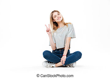 Young woman sitting cross-legged isolated - Young blonde...