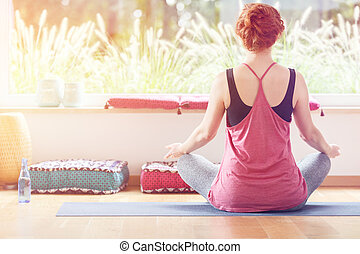 Young woman sitting cross-legged on a sports mat during yoga...