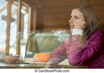 Young woman sitting in a bar alone drinking coffee