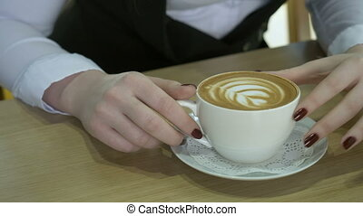 Young woman sitting in a cafe with cappuccino. Coffee...