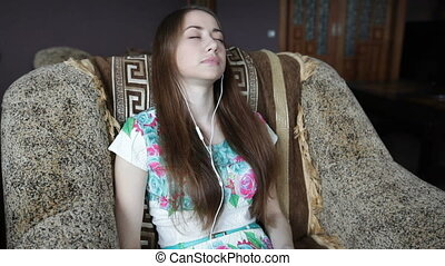 young woman sitting in a chair and listening to music on headphones