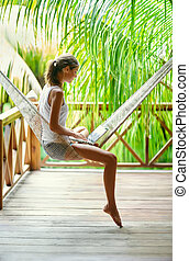 Young woman sitting in a hammock with laptop in a tropical resort. back view.