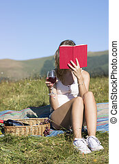 Young woman sitting in a meadow and  reading book